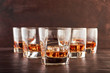 A set of six glasses of whiskey with ice standing on a wooden table. One glass in the foreground, the other glasses in the background with different depth of field.