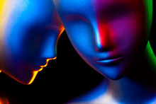 Two Fashion Mannequin Heads Illuminated By Various Colors