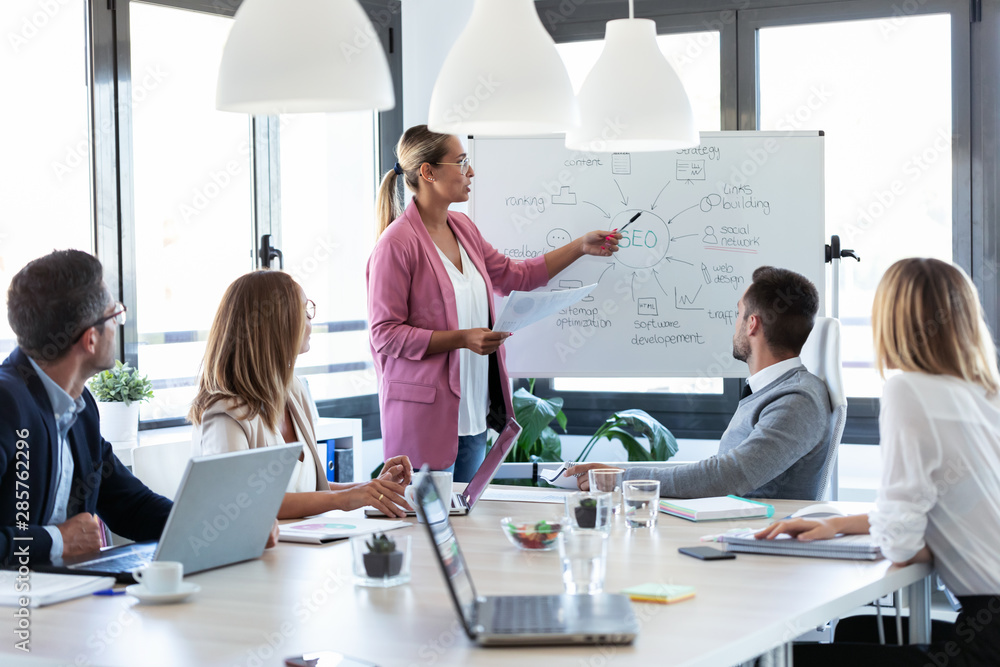 Elegant young businesswoman pointing at white blackboard and explain a project to her colleagues on coworking place.