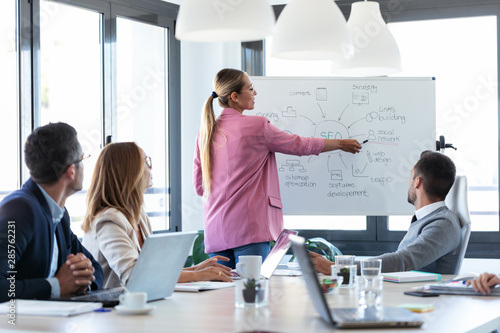 Fototapety, obrazy: Elegant young businesswoman pointing at white blackboard and explain a project to her colleagues on coworking place.