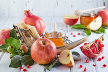 Rosh Hashanah - Jewish New Year Holiday Concept. Traditional Symbols: Honey Jar And Fresh Apples With Pomegranate And Shofar Horn On White Wooden Background. Copy Space For Text.