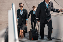 Male Pilot With Suitcase Hurrying For Flight In Airport