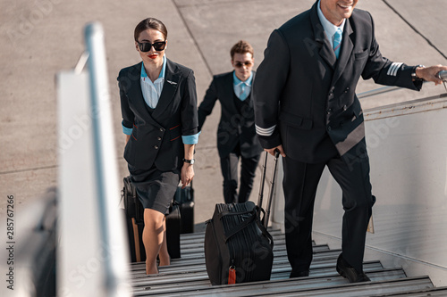 Leinwand Poster Male pilot with suitcase hurrying for flight in airport