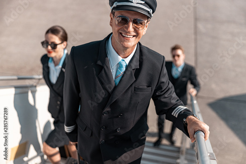 Fototapeta Attractive smiling pilot hurrying for flight in airport
