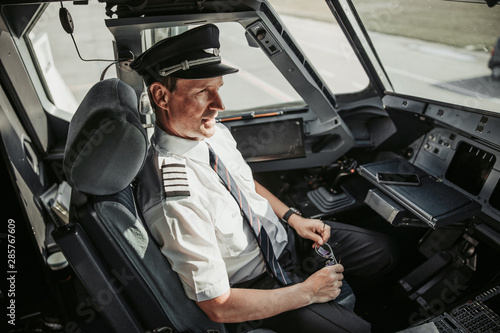 Serious man in uniform looking through window before flight in cockpit Canvas Print