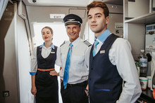 Smiling Caucasian Pilot With Flight Attendants Standing On Airplane Board