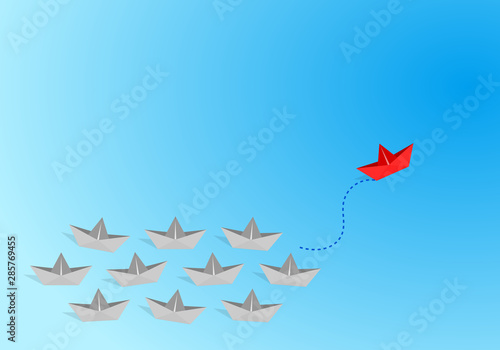 Red origami paper boat leading gray staff ones go on the route on blue background. Leadership and teamwork concept.