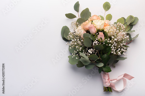 Wedding bride bouquet of cream colored roses isolated on white