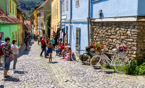 Photo sur Toile Europe de l Est Sighisoara, Romania - 2019. People wandering on the streets of Sighisoara citadel (old town). Streets with colorful houses.