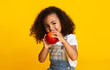 Leinwanddruck Bild - Yummy. Little afro girl eating red apple