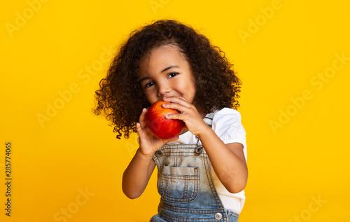 Fototapeta Yummy. Little afro girl eating red apple obraz