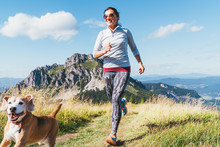 Happy Smiling Female Jogging By The Mounting Range Path With Her Beagle Dog. Canicross Running Healthy Lifestyle Concept Image.