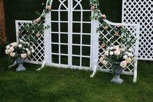 White Wedding Arch Decorated With Flowers