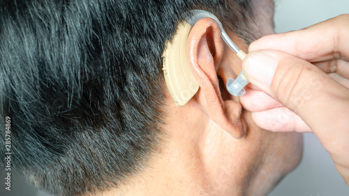 Vászonkép  Deaf old male patient try to wearing modern digital  hearing aid in ear by himse