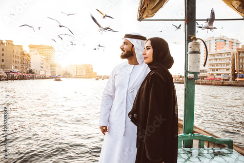 Poster Abou Dabi Happy couple spending time in Dubai. man and woman wearing traditional clothes taking a cruise on the river