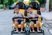 Two Brothers Sit In A Stroller...