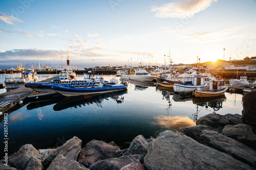 Foto auf AluDibond Schwarz Husavik, Iceland - August 17, 2017: Beautiful view of the historic town of Husavik with traditional houses and traditional fisherman boats lying in the harbor, northern coast of Iceland