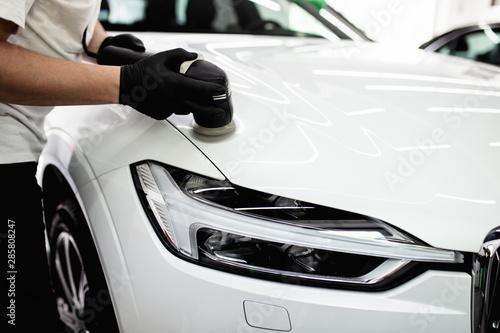 Fototapeta Car detailing - Worker with orbital polisher in auto repair shop. Selective focus. obraz
