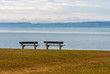 two empty benches on a lake shore