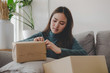 SME startup. asian young entrepreneur woman working and packing cardboard parcel box for send order to customer at home office, shopping online, small business owner, logistics and delivery concept