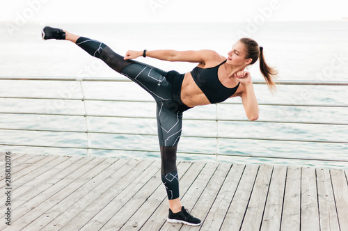 Fotografía Muscular woman fighter in sportswear makes kick on the beach terrace against the