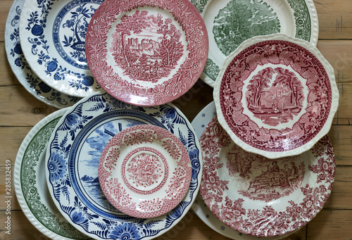 Foto Vintage porcelain plates in different sizes and colors on a wooden background