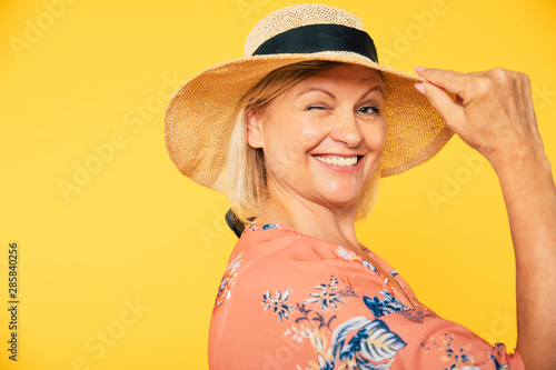 Fototapeta Beautiful smiling and happy cute senior woman in colorful clothes is posing on yellow background. Holidays and vacation. Summer mood obraz