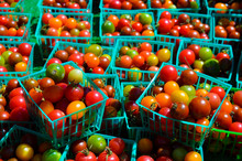 Many Different-colored Tomatoes Sit In Green Baskets At A California Farmer's Market.
