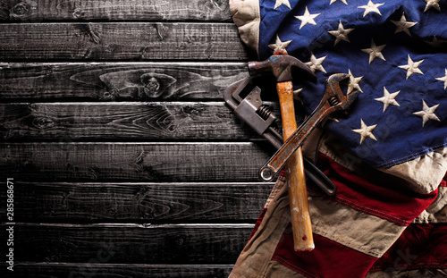 Photo Stands Countryside Old and worn work tools on large American flag - Labor day background