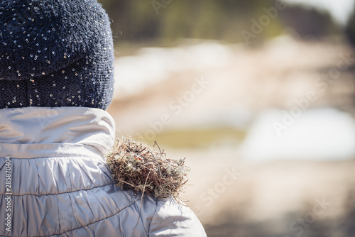 Valokuvatapetti Breeding nest made by birds from grass, branches and pine needles on the shoulder of girl in the forest