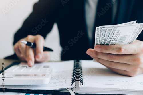 Fotomural  Investors are calculating on calculator investment costs and holding cash notes in hand