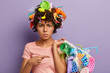 canvas print picture - Photo of displeased Afro American woman angry with abusive use of plastic, points at bag with collected garbage, has wastes in head, isolated on purple wall. Non recyclable pollution concept