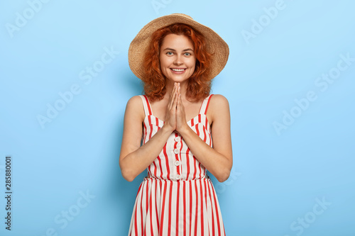 Valokuva  Lovely young female models indoor, keeps palms pressed together, being thankful for help, wears summer striped dress, straw hat, looks happily at camera, isolated on blue wall