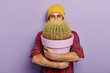 Leinwandbild Motiv Photo of happy young male flower grower embraces big pot with prickly cactus, wears stylish hat and checkered shirt, glad to receive house plant as gift, isolated on purple wall. Gardening concept