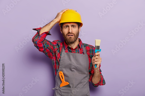 Cuadros en Lienzo Disappointed industrial worker dressed in safety hardhat, casual uniform, holds