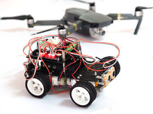 Closeup Shot Of Electronic Car Controlled By Programming With Sensors With Blurred Drone Background.