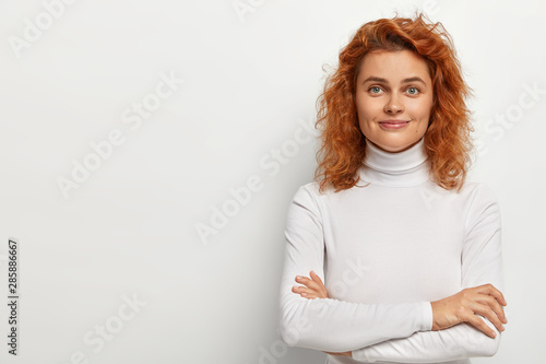 Fototapety, obrazy: Portrait of good looking redhead woman looks with little smile, has calm face expression, keeps arms folded, wears white turtleneck, poses alone, listens pleasant comments, isolated on white wall