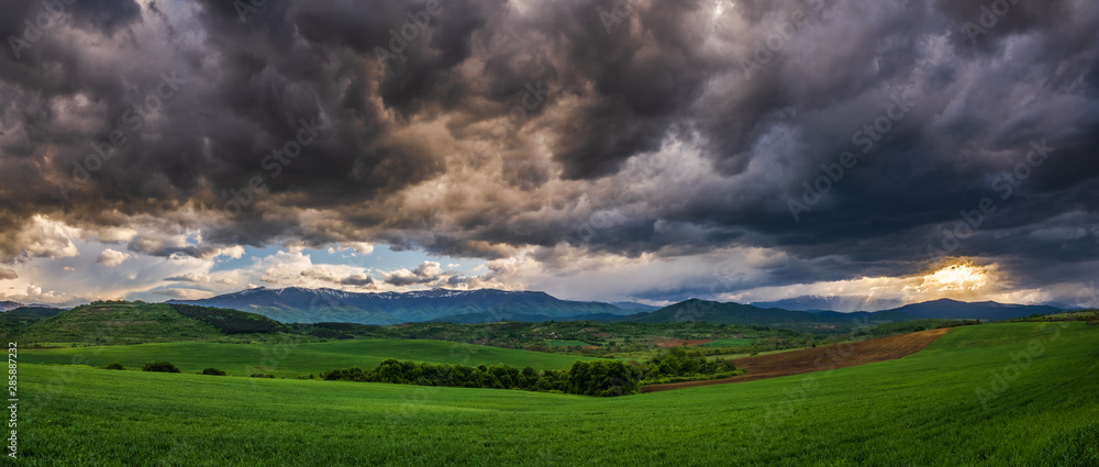 Fototapeta Panoramic view of uneven green agriculture fields in the foreground, distant mountain range in the background, and heavy stormy overcast dramatic clouds in the sky