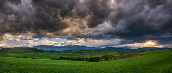 Panoramic view of uneven green agriculture fields in the foreground, distant mountain range in the background, and heavy stormy overcast dramatic clouds in the sky