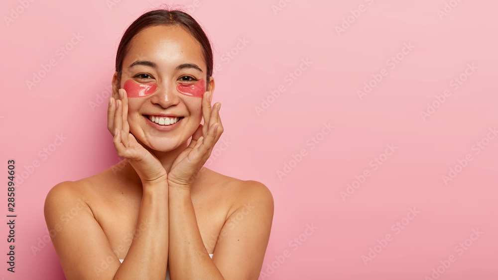 Fototapeta Portrait of cheerful korean woman smiles happily, applies cosmetic patches under eyes, touches cheeks gently, has healthy skin, cares about her beauty, poses shirtless against pink background