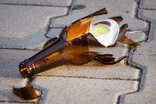 Bottle Of Beer, Soda Or Drugs From Dark Glass Is Broken. Shattered Beer Bottle On Ground In Sunset Light. Fragments Of Glass On Asphalt. Texture, Background, Wallpaper.