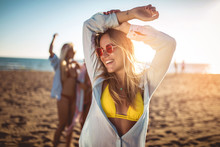 Happy Young Woman On The Beach With Her Friends In Background. Group Of Friends Enjoying On Beach Holiday.