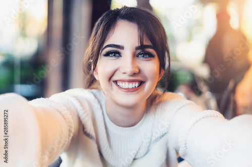 Fotomural Smiling girl taking selfie with her hands for social networks while sitting in cafe