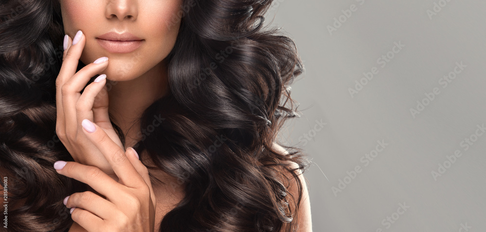 Fototapeta Beauty brunette girl with long  and   shiny wavy black hair .  Beautiful   woman model with curly hairstyle .Pearly manicure on nails