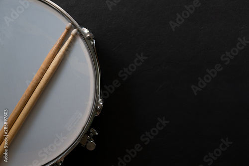 Drum stick and drum on black table background, top view, music concept Fototapeta