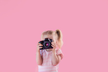 Little Pretty Girl Photographer On Pink Background Shooting With Professional Photo Camera