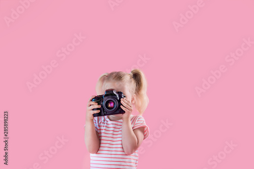 Obraz Little pretty girl photographer on pink background shooting with professional photo camera - fototapety do salonu