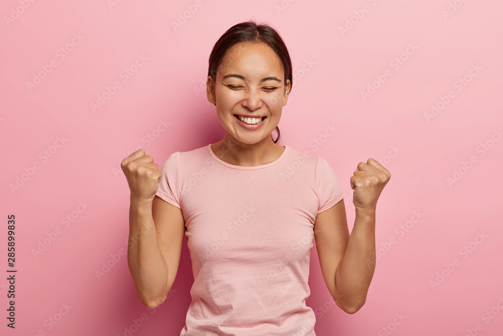 Fototapeta Successful emotional Asian woman clenches fists in air, celebrates success, has broad smile, keeps eyes closed, being excited and joyful, enjoys sweet taste of victory, wears casual clothes.