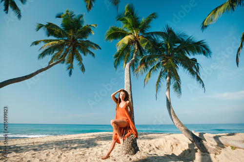 Photo sur Aluminium Palmier Summer lifestyle portrait of pretty happy young girl with tanned sexy body. Relax, smiling and sitting on palm tree at the tropical island beach with clear water. Wearing red dress, closed eyes