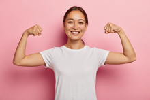 Pretty Korean Female Model Keeps Fit And Healthy, Raises Hands And Shows Muscles, Feels Proud About Her Achievements In Gym, Smiles Broadly, Dressed In White Casual Wear, Poses Indoor Shows Real Power